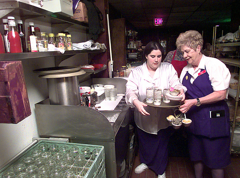 Christina Posey, left, a junior at PIne Tree High School, also known as the water girl at Johnny Cace's in Longview, helps Bertie Brooks, right, a service for the past 18 years, Friday afternoon in Longview, Christina was part of the Hospitality Program at Pine Tree prior to being hired on at Cace's. Kevin green