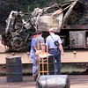 7/7/99---TNRCC environmental investigator Dale Vodak, right, visit with two unidentified men while looking at what remains of a flatbed truck after the driver lost control and the truck flipped causing 44 55 gallon drums to be spilled Wednesday morning along 259 in Rusk County. Kevin green