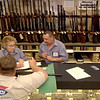 Academy Sports and Outdoors employees Sue Pittman, left, Vernon Orms, right, and Tim Trice, forground, go over firearms purchasing paperwork Wednesday September 12, 2001 as the continue to train prior to tomoorow's opening of the store in Longview. Kevin green