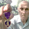 6/4/99---E.E. Blackan Army vet holds his purple heart he recieved for being wounded in the line of duty during the D-Day war. Kevin green